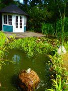 Gartenhaus-am-Teich-mit-Quellstein-und-Holzterrasse